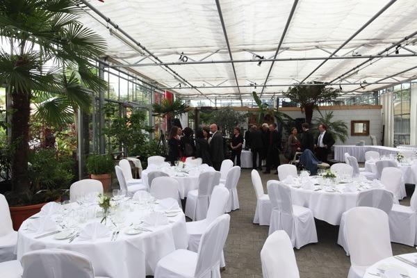 Runde Tische im Plangarten für eine Hochzeit. Im Hintergrund stehen Gäste