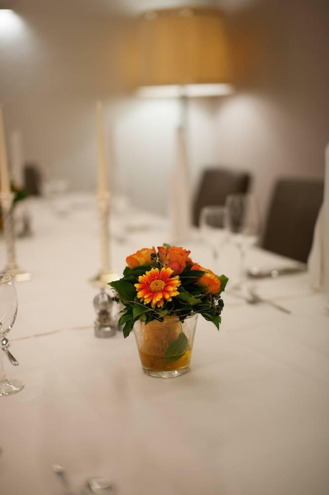 Fokus auf einer Blume auf dem Tisch. Tisch und Lampe unscharf