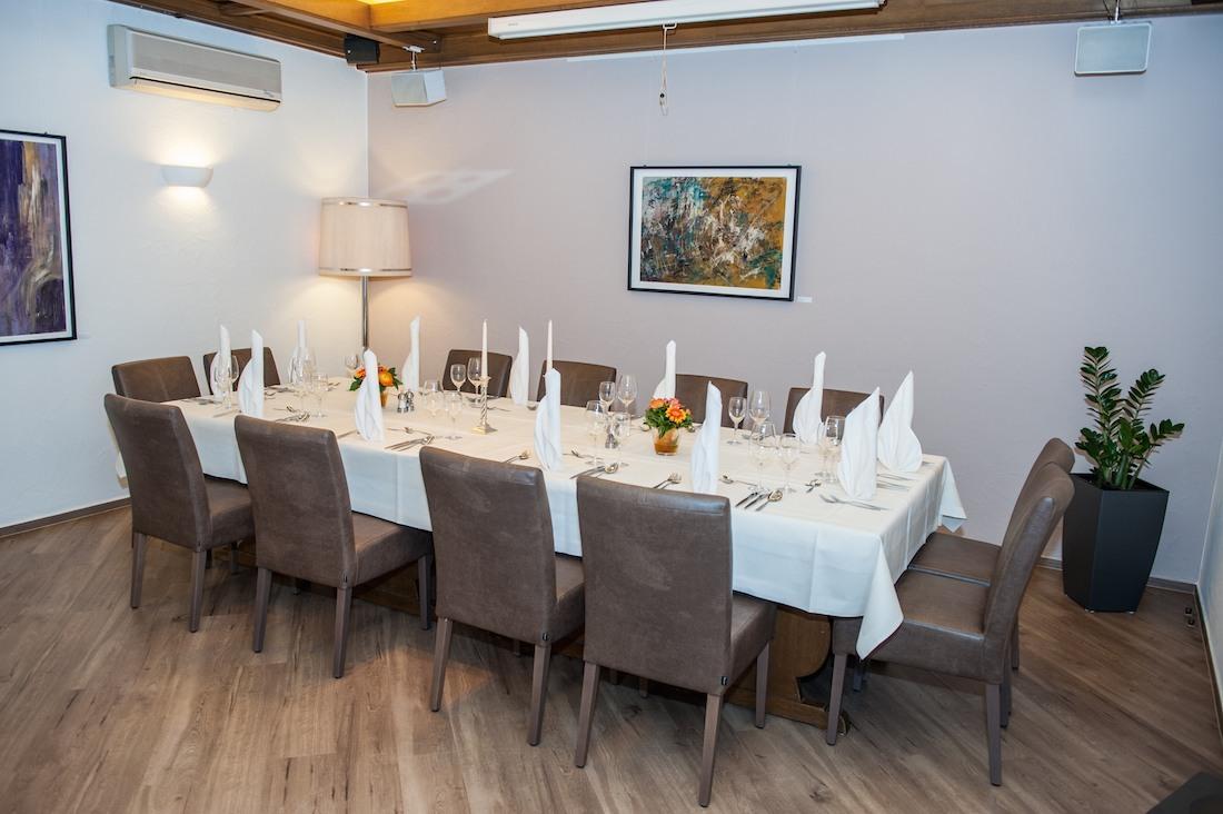 festlich gedeckter Tisch mit dunklen Stühlen